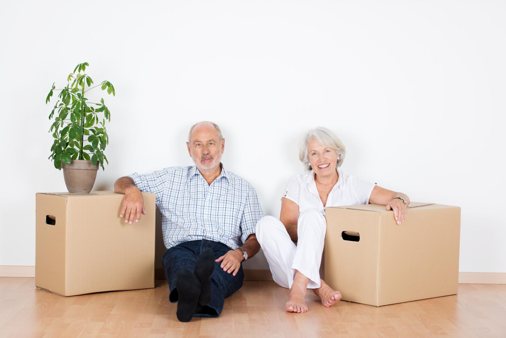 senioren-paar sitzt lchelnd zwischen umzugskartons